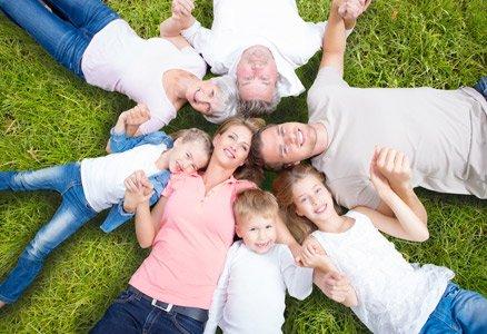 drei Generationen-Familie liegt im Gras