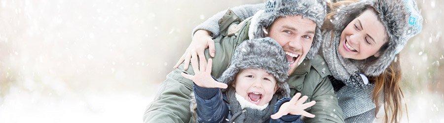glückliche Familie mit Kleinkind im Schnee