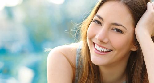 glückliche junge Frau mit dunklem Haar lächelt entspannt