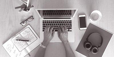 schreibende Frau auf Laptop mit Stift und Block