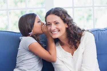 Tochter flüstert Mutter etwas ins Ohr
