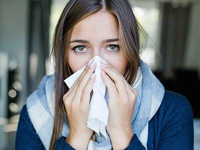 erkältete Frau schnäuzt die Nase