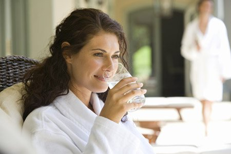 Frau im Bademantel trinkt stilles Wasser