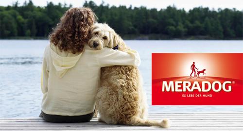 Frau schmust mit ihrem Hund am See