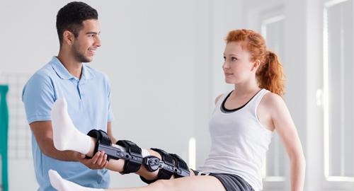 Physiotherapeut macht Bein-Übungen mit Frau